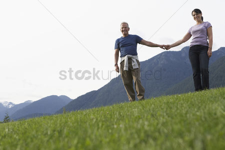 British ethnicity : Portarit of couple holding hands mountain range in background
