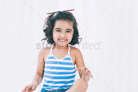 Satisfying : Portrait of a girl smiling with a pencil on her head