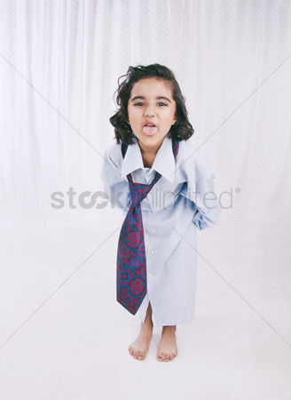 Bliss : Portrait of a girl wearing oversize shirt with tie and sticking her tongue out