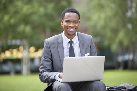 Business suit : Portrait of a happy african american businessman using laptop in park