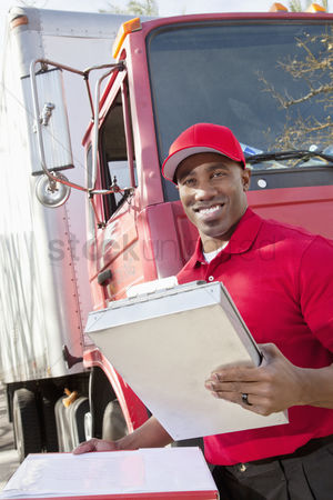Truck : Portrait of a happy african american man holding clipboard with delivery truck in background
