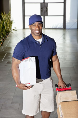 Pushing : Portrait of a happy delivery man with packages
