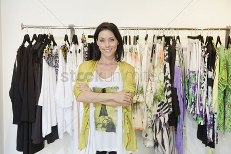 Beautiful people : Portrait of a happy mid adult woman with arms crossed in front of clothes rack