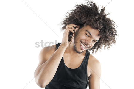 Portability : Portrait of a happy young man listening to mobile phone over white background