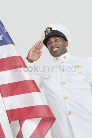 Respect : Portrait of a happy young us navy officer saluting american flag over gray background