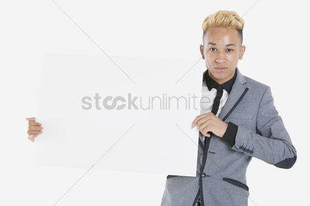 Cardboard cutout : Portrait of a teenage boy holding blank cardboard over gray background