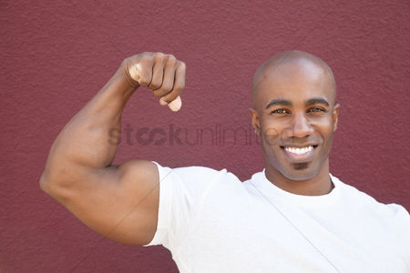 Bald : Portrait of a young african american man flexing muscles over colored background
