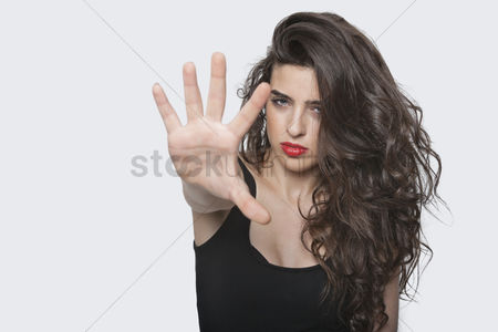 Attitude : Portrait of a young female gesturing stop sign over gray background