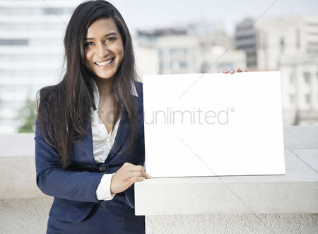 Smile : Portrait of a young indian businesswoman holding moodboard sign