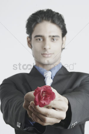 Man suit fashion : Portrait of a young man holding out a rose