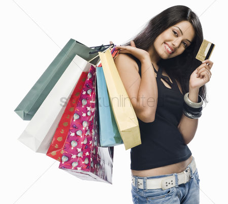 Spending money : Portrait of a young woman holding shopping bags