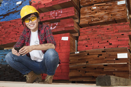 Asian : Portrait of an asian female industrial worker holding cell phone with stacked wooden planks in background