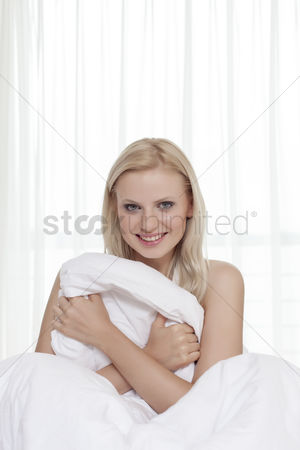 Shyness : Portrait of attractive young woman holding bedsheet in bed