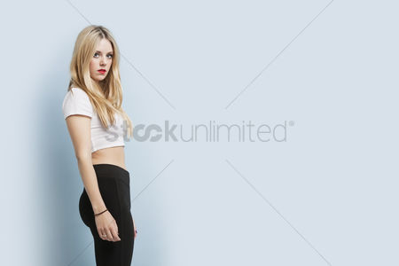 Women : Portrait of beautiful young blond woman with red lips standing against blue background
