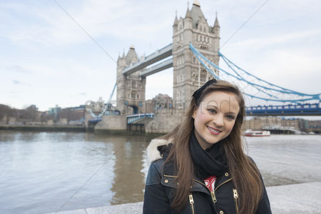 England : Portrait of beautiful young woman standing in front of tower bridge  london  uk