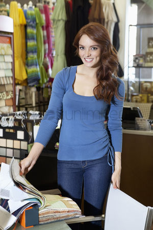 Supermarket : Portrait of beautiful young woman standing with textile samples in store