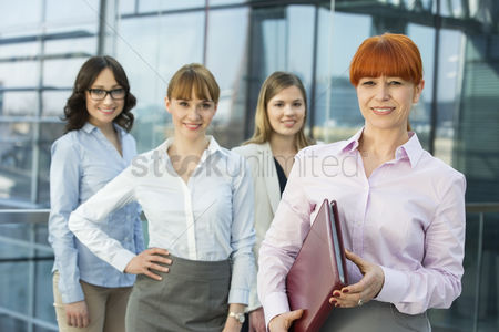Leadership : Portrait of confident businesswoman holding folder with female colleagues standing in background