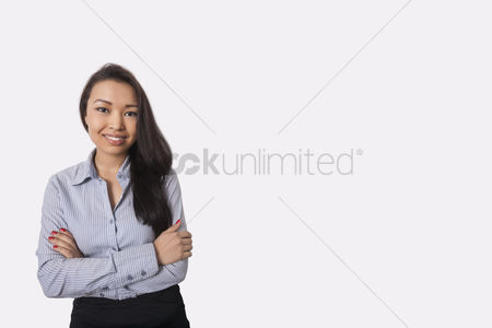 Office worker : Portrait of confident businesswoman standing arms crossed against gray background