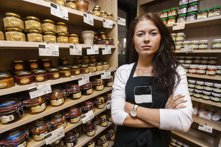 Supermarket : Portrait of confident saleswoman standing arms crossed in grocery store