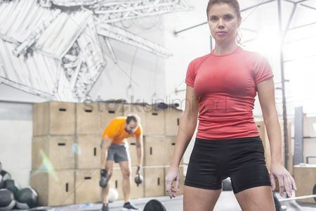 Mid adult man : Portrait of confident woman standing in crossfit gym