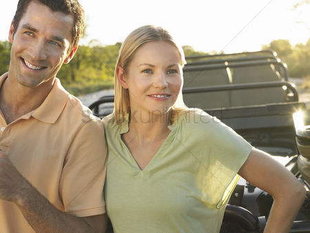 On the road : Portrait of couple outdoors standing by jeep smiling