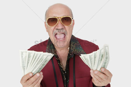 Man suit fashion : Portrait of excited senior man showing us banknotes with mouth open against gray background
