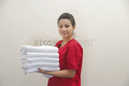 Pile : Portrait of female housekeeper holding clean white towels against gray background