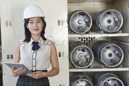 Forklift : Portrait of female industrial worker holding tablet pc with cylinders on shelf in background