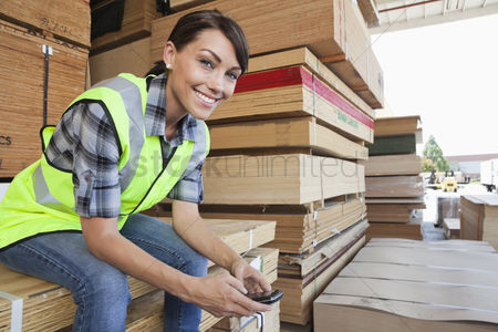Smiling : Portrait of female industrial worker using cell phone while sitting on stack of wooden planks
