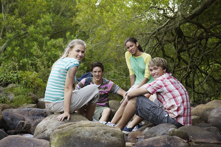 Group portrait : Portrait of four teenagers  16-17 years  sitting on stones by river smiling