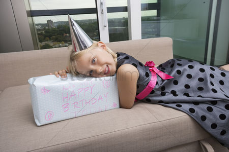 Birthday present : Portrait of girl with birthday gift lying on sofa at home