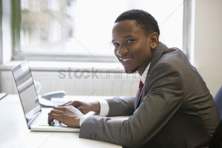 Internet : Portrait of happy african american businessman using laptop at office desk