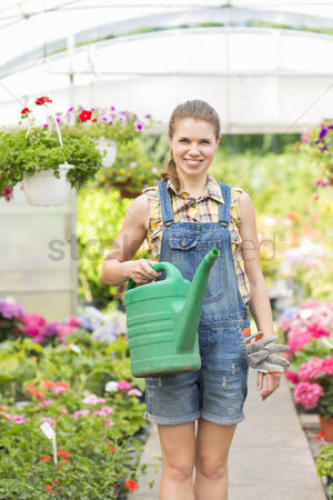 Greenhouse : Portrait of happy female gardener holding watering can in greenhouse