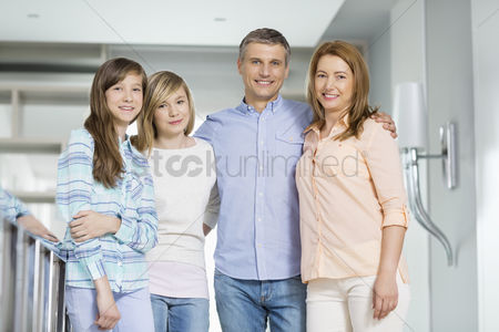 Three quarter length : Portrait of happy parents with daughters standing together at home