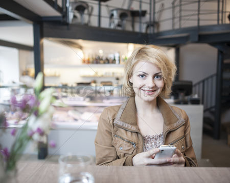 Czech republic : Portrait of happy young woman using cell phone in cafe