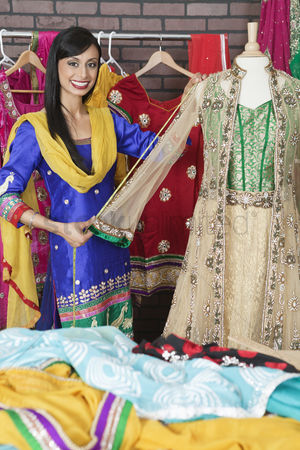 Traditional clothing : Portrait of indian designer measuring traditional outfit at design studio