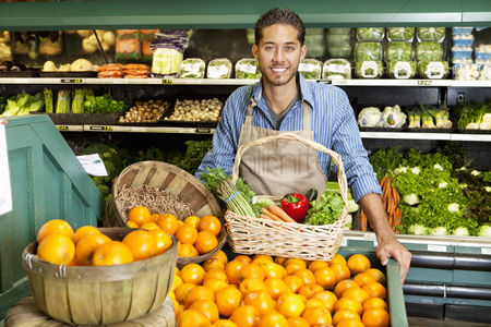 Variety : Portrait of man in supermarket with vegetable basket standing near oranges stall