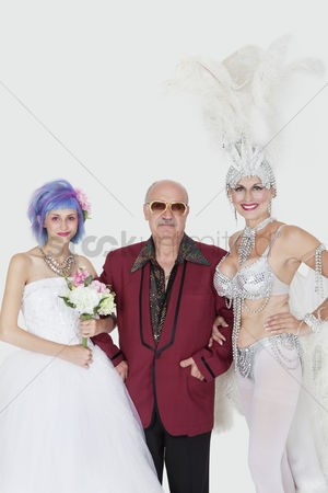 Man suit fashion : Portrait of man standing arms in arms with senior showgirl and daughter in wedding dress over gray background