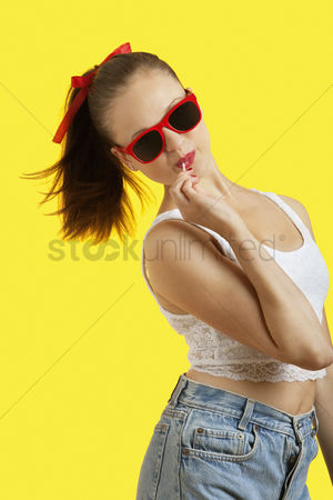 Ponytail : Portrait of playful young woman in sunglasses eating lollipop over yellow background