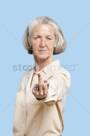 Senior women : Portrait of senior woman in casuals making rebellious gesture against blue background