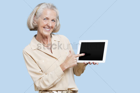 Blue background : Portrait of senior woman showing tablet pc against blue background