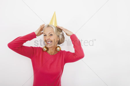 Celebrating : Portrait of senior woman wearing party hat and christmas ornaments over white background