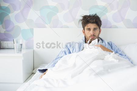 Thermometer : Portrait of sick man with thermometer in mouth reclining on bed at home