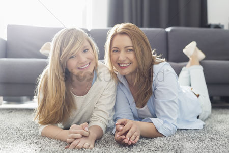 Daughter : Portrait of smiling mother and daughter lying on carpet