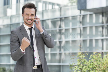 Business suit : Portrait of successful young businessman using cell phone against office building