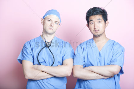 British ethnicity : Portrait of two male surgeons standing with arms crossed over pink background