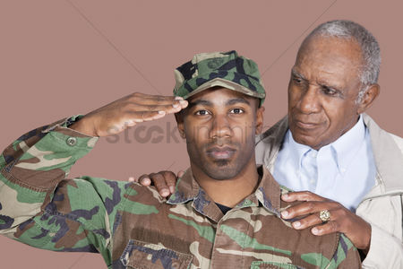 Respect : Portrait of us marine corps soldier with father saluting over brown background