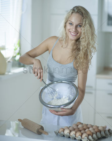 Egg tray : Portrait of woman mixing cookie batter in kitchen at counter