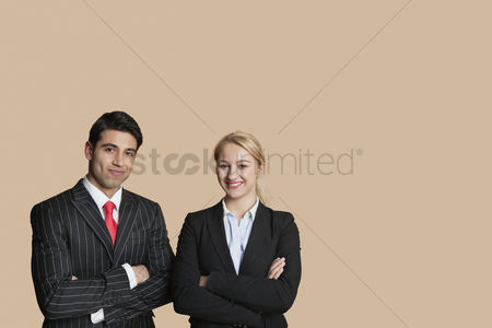 Two people : Portrait of young business team with arms crossed over colored background