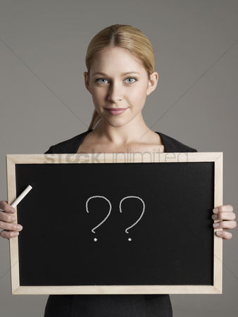 Ideas : Portrait of young businesswoman holding blackboard with question marks